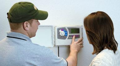 Homestead FL irrigation contractor shows a homeowner how to set her Rain Bird sprinkler timer
